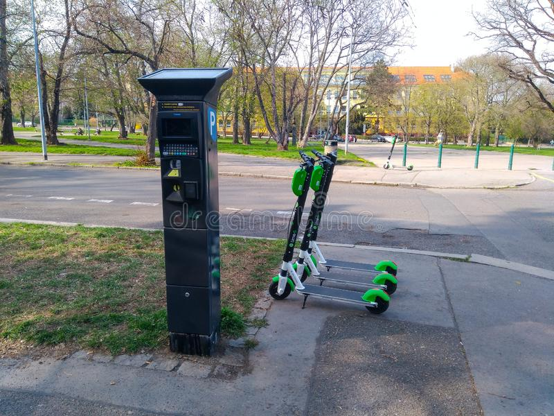 Eletro scooters stand near the parking machine stock photography