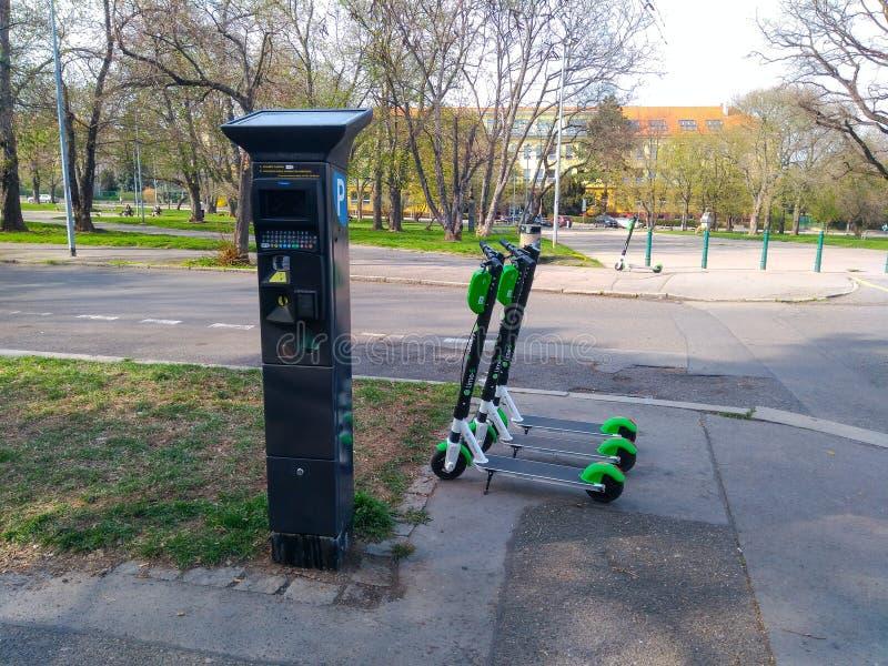 Eletro sparkcyklar står nära den parkera maskinen arkivbild