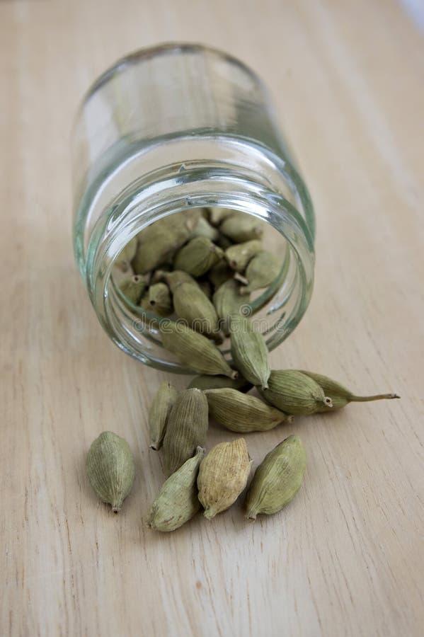 Elettaria cardamomum trägt, wahres Kardamom des Grüns, verarbeitete Kardamomhülsen auf Holztisch Früchte stockfoto