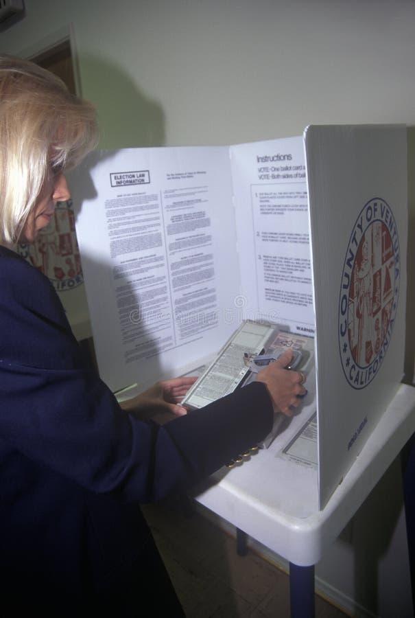 Elettore della donna in una cabina di voto che seleziona le scelte su un voto, CA fotografia stock libera da diritti