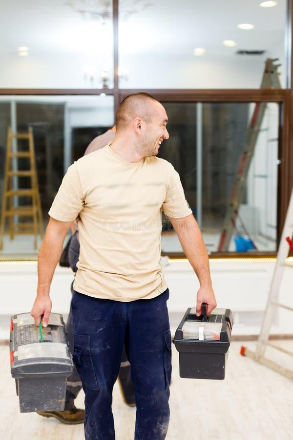 Elettricista Carrying Tool Boxes dopo lavoro fotografie stock