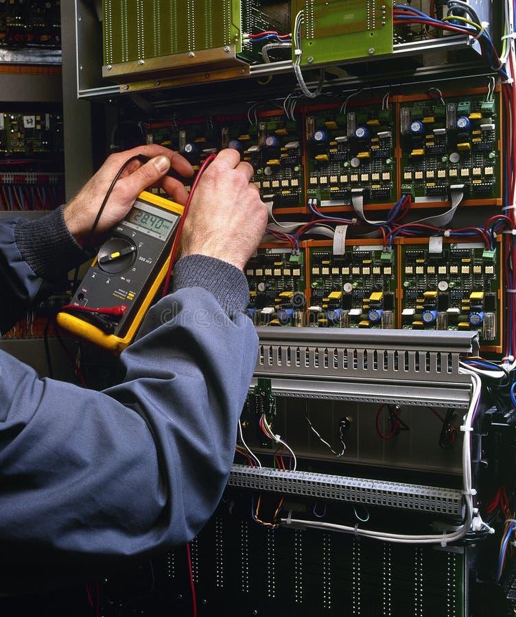 Elettricista che collauda macchina industriale immagine stock