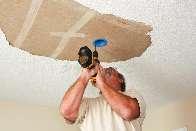 Elettricista che installa lampada sul soffitto immagini stock