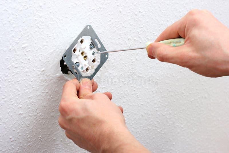 Elettricista che installa lo zoccolo di parete fotografia stock libera da diritti