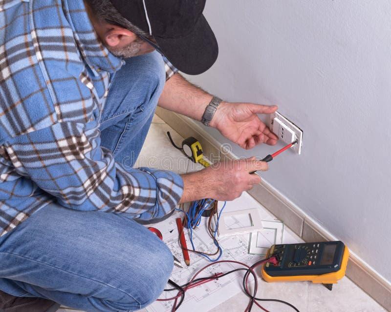 Elettricista che lavora nella pianta elettrica fotografia stock