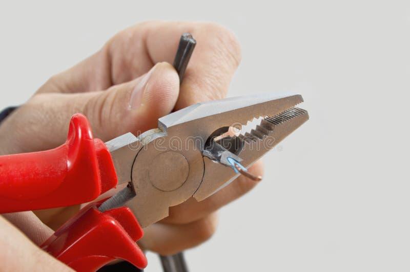 Elettricista che taglia un cavo. immagini stock