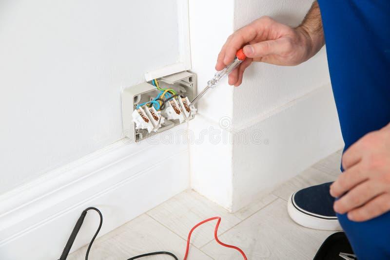 Elettricista con il tester della neon-lampada che controlla tensione all'interno fotografie stock