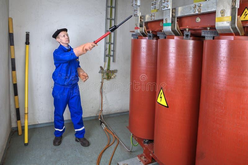 Elettricista Engineer che usando sti ad alta tensione elettrico del rivelatore fotografia stock libera da diritti