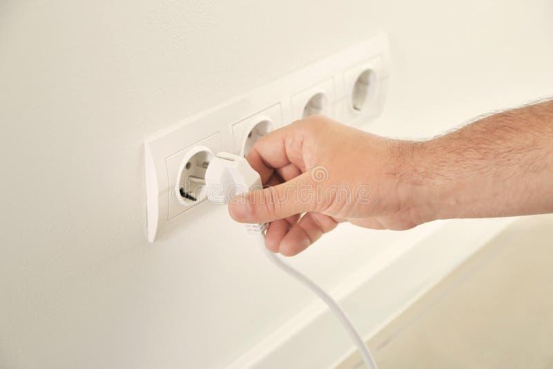 Elettricista maschio che inserisce spina nell'incavo per controllare la sua utilità, primo piano immagine stock libera da diritti