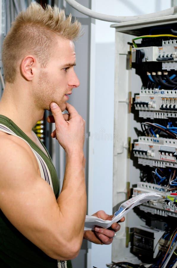 Elettricista maschio confuso davanti al pannello di potere fotografie stock libere da diritti