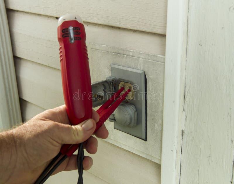 Elettricista Testing uno sbocco esterno fotografia stock libera da diritti