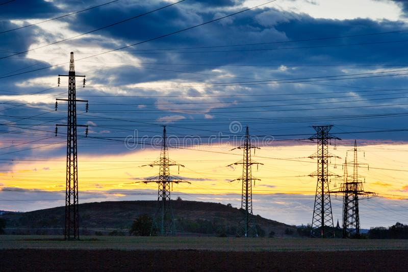 Elettricità - industria energetica di potere - pali elettrici ai soli fotografia stock libera da diritti