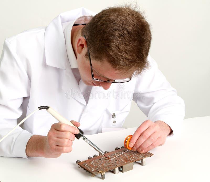 Elettronica di lavoro che ripara bordo che usando penna di saldatura immagini stock