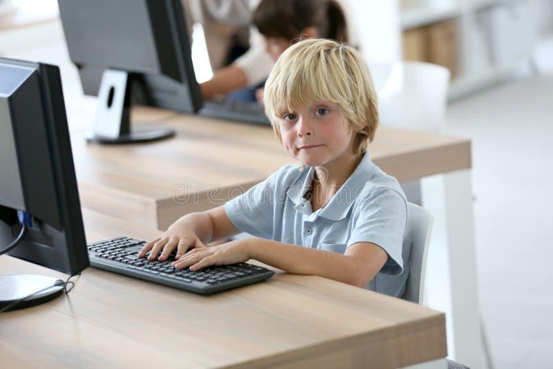 Elev för skolapojke som lär hur man använder datoren arkivbilder