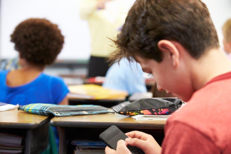 Elev som överför textmeddelandet på mobiltelefonen i grupp royaltyfria bilder