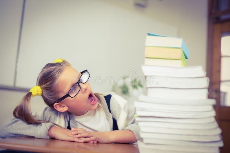 Elev som ser chockad på bunten av böcker på hennes skrivbord royaltyfri foto