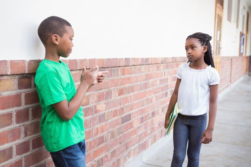 Elev som trakasserar andra i korridoren arkivfoto