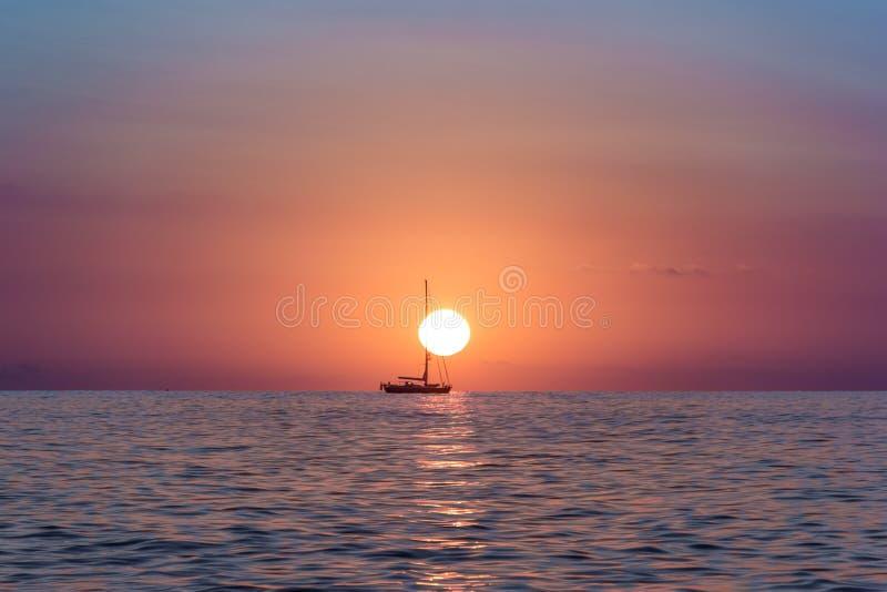 Elevação de Sun no oceano com um barco que flutua na frente do sol fotos de stock