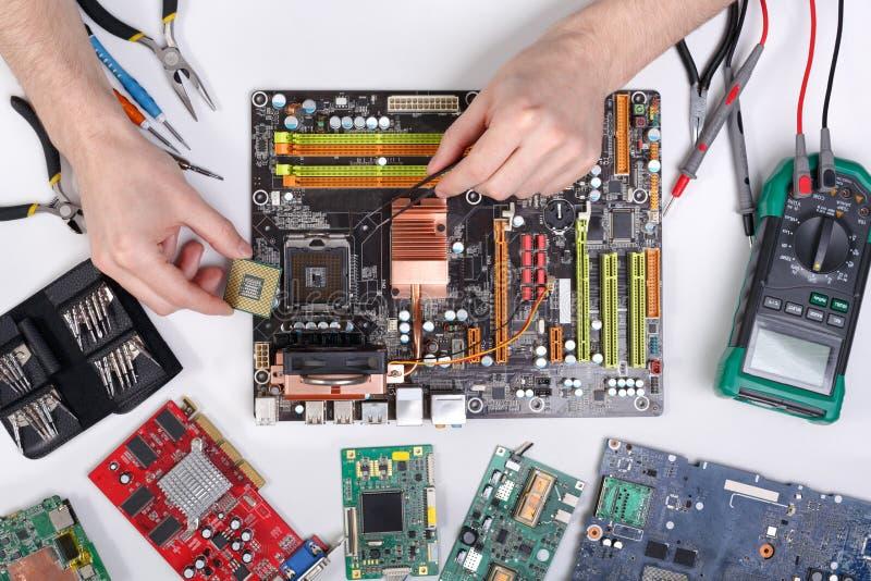 Elevação do computador O técnico obstrui dentro o microprocessador ao motherboa imagens de stock royalty free