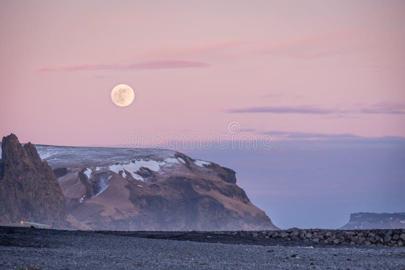 Elevação do por do sol e da lua sobre a praia da areia das montanhas e do preto de Vik's em Islândia fotografia de stock royalty free