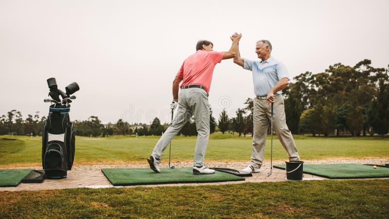Elevação superior cinco dos jogadores de golfe no driving range imagens de stock royalty free