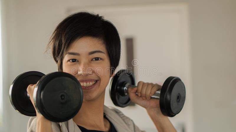 Elevación asiática sonriente de la pesa de gimnasia de la aptitud de la mujer del pelo corto exercis imagenes de archivo