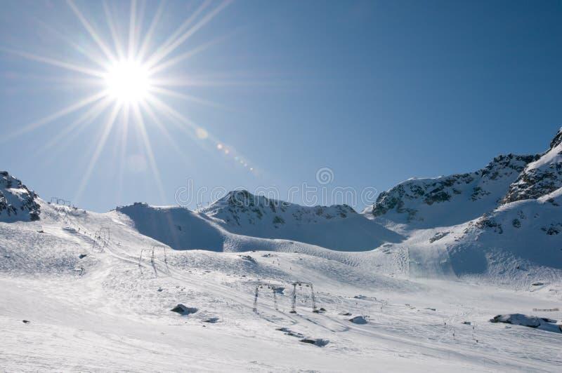 Elevación de esquí en el centro turístico de la alta altitud, sol con la flama imágenes de archivo libres de regalías