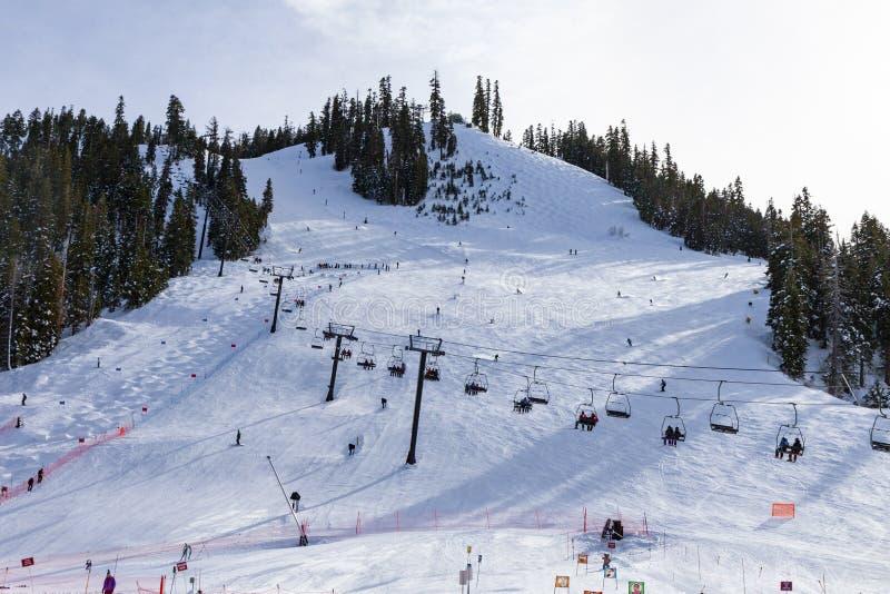 Elevación de silla de Squaw Valley Ski Resort con la gente sking cuesta abajo foto de archivo
