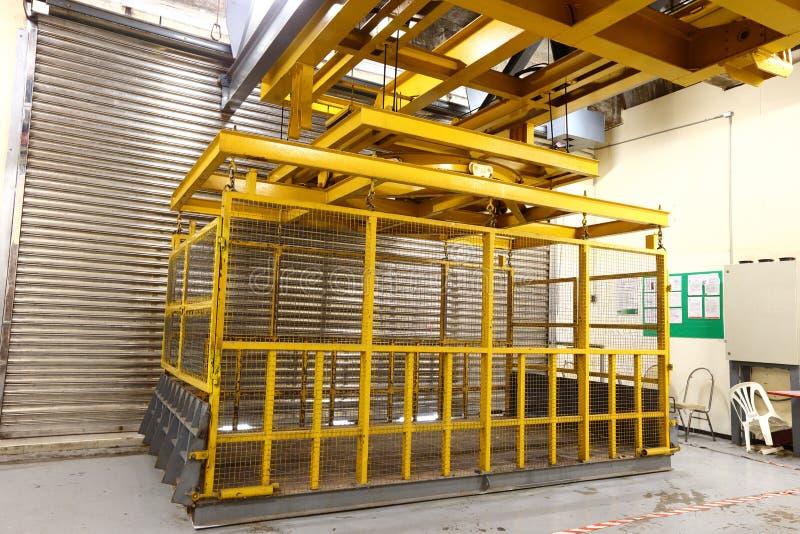 Elevador amarillo en la bahía de cargamento para cargar la máquina pesada dentro del buil fotografía de archivo libre de regalías