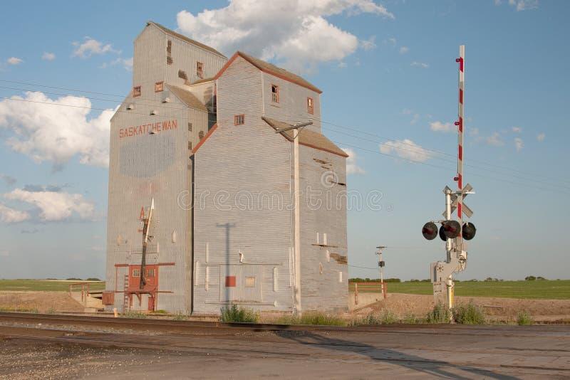 Elevador de grão perto do cruzamento de estrada de ferro imagens de stock royalty free