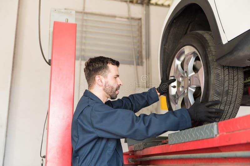Elevador de Servicing Car On do técnico na garagem imagens de stock royalty free