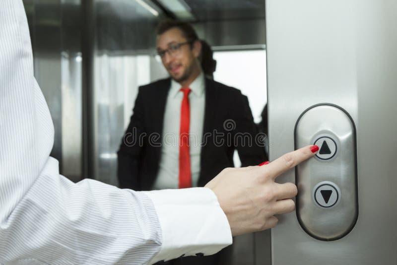 Elevador fêmea da pressão de mão acima do botão Homem de negócios dentro do elevador fotos de stock