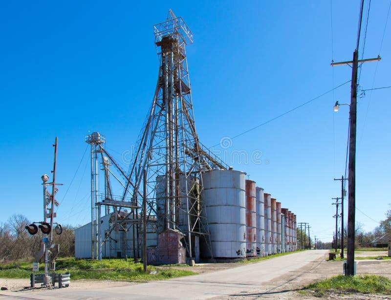 Elevadores de grano al lado de una travesía de ferrocarril foto de archivo