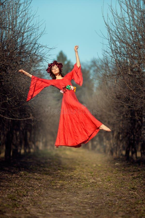 Elevar y mantener flotando a la muchacha entre los árboles imagen de archivo libre de regalías