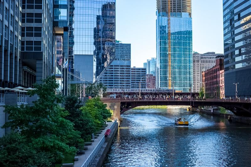 Elevated `el` train and water taxi carry commuters, along with pedestrians walking during morning commuter over Chicago River. During summer stock photos
