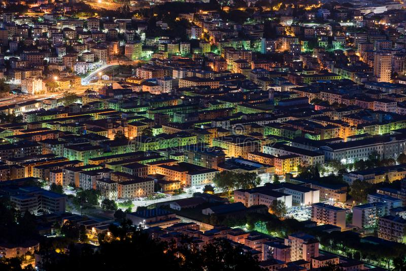 Elevated rooftop night view of La Spezia, Italy. With colorful illuminated lights in the buildings in a travel and tourism concept stock photography