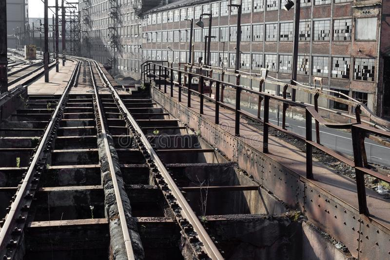 Elevated train tracks running alongside and abandoned industrial complex stock photography