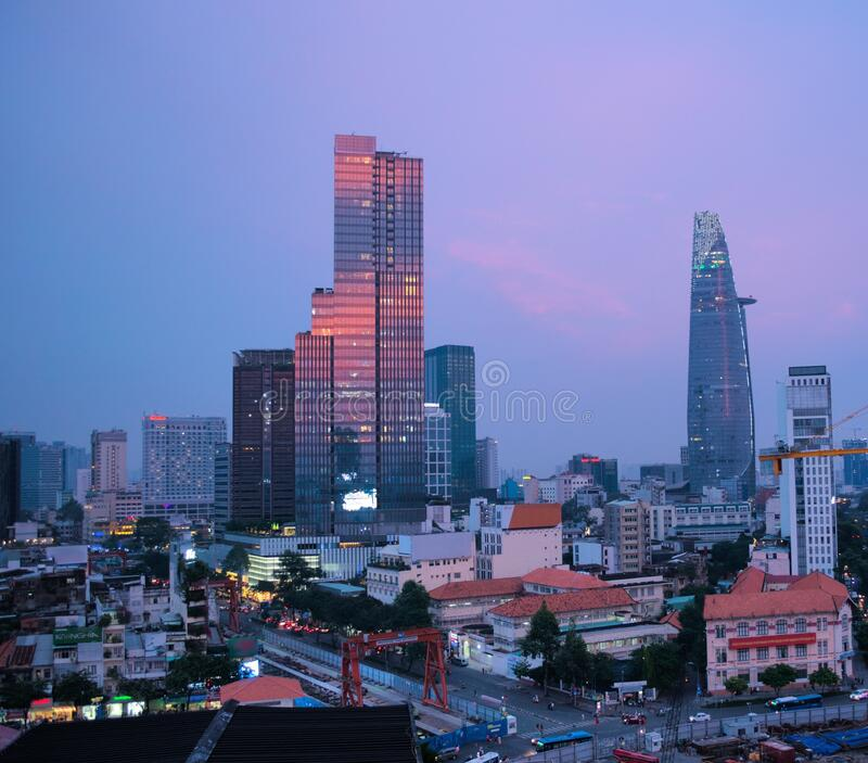 Elevated view of the city of Saigon, Vietnam Ho Chi Minh City at twilight. Pink clouds can be seen reflected on a tall, modern b. Uilding royalty free stock image