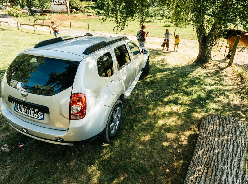 Elevated view Dacia Duster SUV in green fild French mountains under tree stock photo
