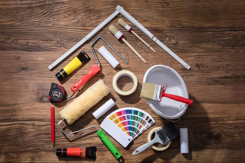 House Made With Painting Equipments And Measuring Tape. Elevated View Of House Made With Painting Equipments And Measuring Tape On The Wooden Table stock photography