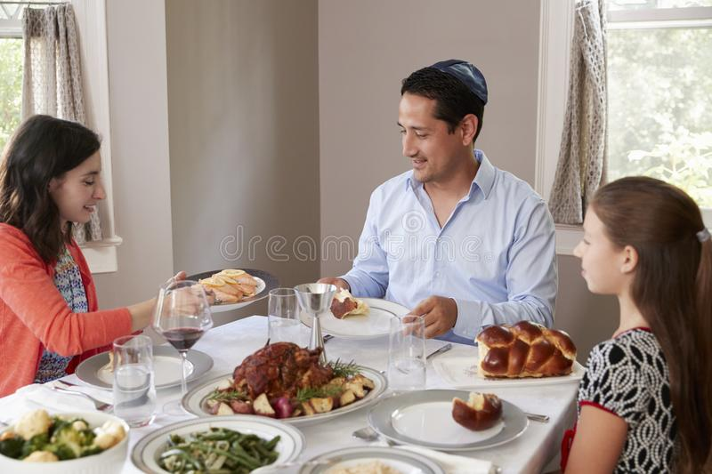 Elevated view of Jewish family serving food at Shabbat meal royalty free stock photo