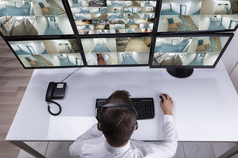 Security Guard Monitoring Multiple Camera Footage On Computer royalty free stock photography