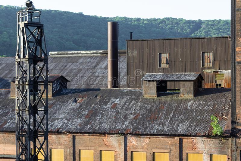 Elevated view of manufacturing warehouse buildings of brick and corrugated metal, mountains behind stock photography