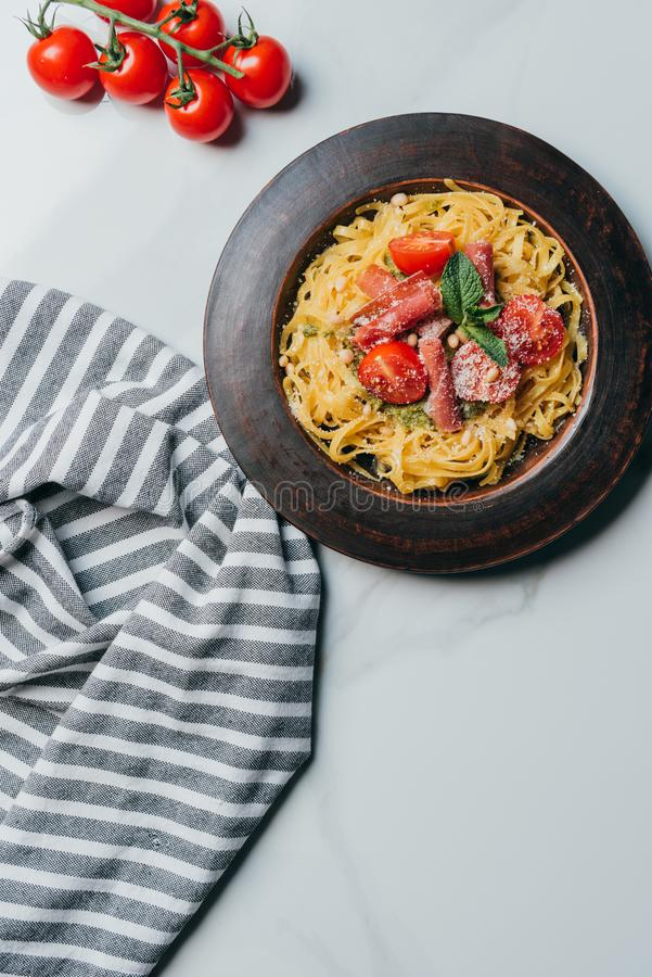 elevated view of pasta with mint leaves, jamon and cherry tomatoes covered by parmesan on plate at marble table stock image