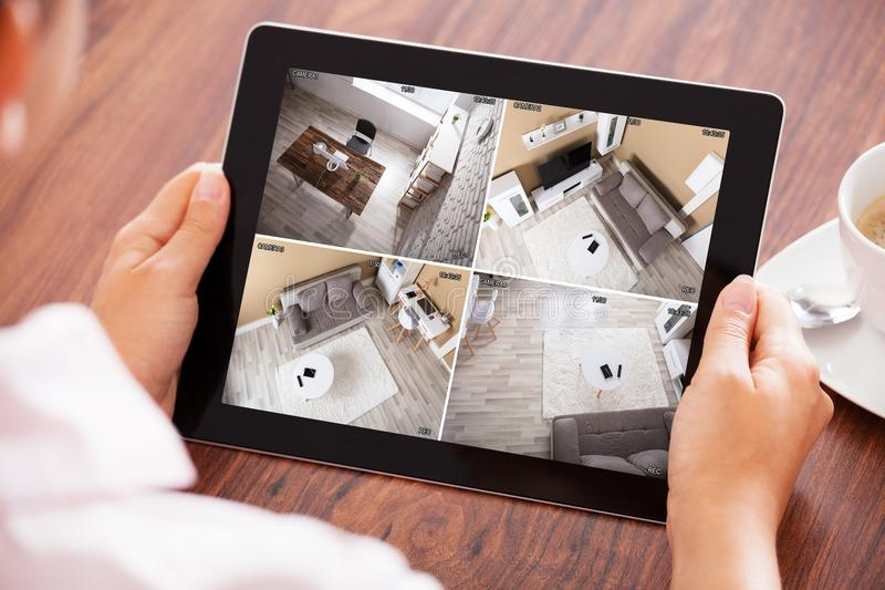 Person`s Hand Looking At Home Security Cameras. Elevated View Of A Person`s Hand Looking At Home Security Cameras On Tablet stock photography