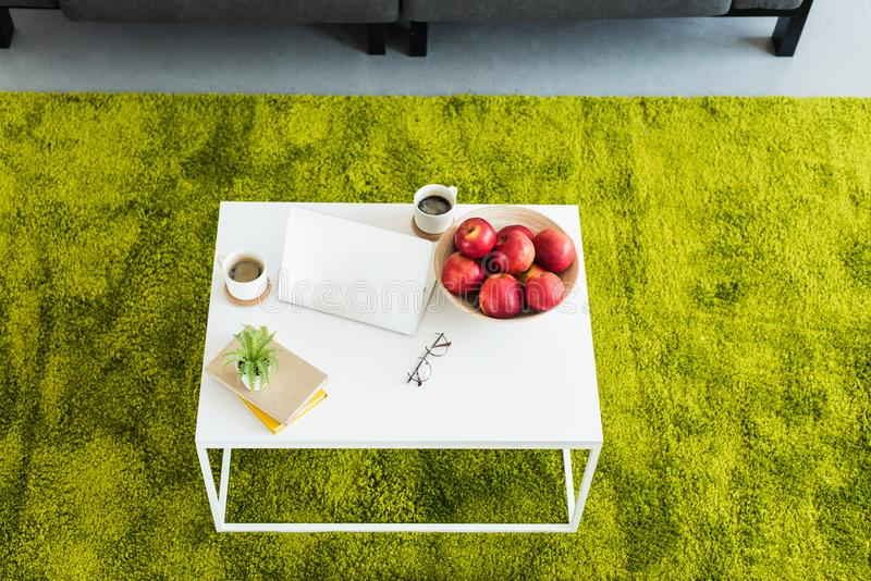 elevated view of table with laptop, coffee cups, apples in bowl, books, eyeglasses and plant royalty free stock photo