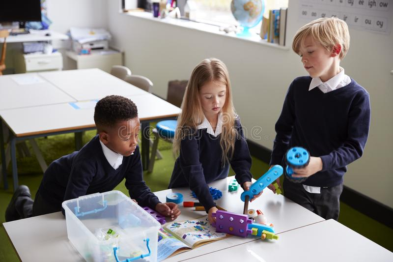 Elevated view of three primary school kids standing at a table in a classroom, working together with toy construction blocks royalty free stock photo
