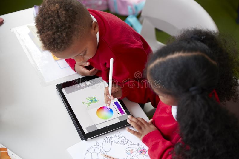 Elevated view of two kindergarten school kids sitting at a desk in a classroom drawing with a tablet computer and stylus, close up royalty free stock image