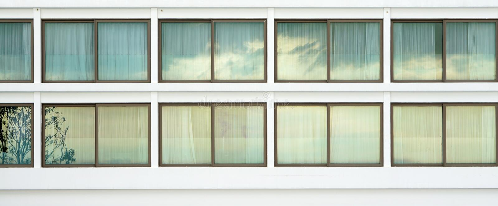Elevation of the generic large sliding window with brass frame o. N the white building reflected tree and cloud royalty free stock photos
