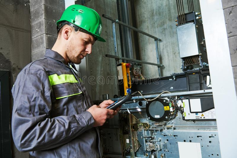 Lift machinist repairing elevator in lift shaft. Elevator installation and maintenance. lift machinist worker adjusting elevator mechanism with remote control in royalty free stock image
